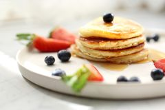 Homemade pancakes with strawberries, blueberries and maple syrup. Sweet breakfast royalty free stock photos