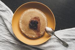 Homemade pancakes on the yellow plate with cherry jam Royalty Free Stock Photography