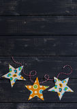 Homemade paper Christmas garland on a dark wooden surface. Royalty Free Stock Photography