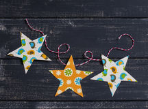 Homemade paper Christmas garland on a dark wooden surface. Royalty Free Stock Photo
