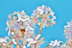 Homemade paper flowers on a background of bright blue sky.  Royalty Free Stock Photo