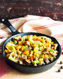 Homemade pappardelle pasta dish with pumpkin, avocado, chili pepper and pork meat. In a pan on a wooden table, selective focus Royalty Free Stock Photo