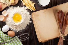 Homemade pasta cooking. And old cooking book on wooden table. Top view with copy space Stock Photo