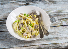 Homemade pasta with creamy mushroom sauce on a light wooden background. Homemade pasta with creamy mushroom sauce on a light blue wooden background Royalty Free Stock Images