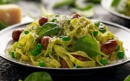 Homemade Pasta with green peas, spinach pesto and sausages. parmesan cheese. healthy food. close up royalty free stock photo