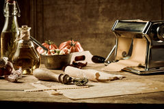 Homemade pasta making scene with tomatoes Royalty Free Stock Photography