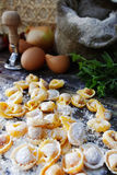 Homemade pasta ravioli on old wooden table with flour, eggs, kit. Chen italian herbs - cooking concept Royalty Free Stock Image