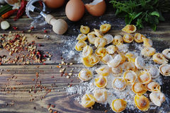 Homemade pasta ravioli on old wooden table with flour, eggs, kit. Chen italian herbs - cooking concept Royalty Free Stock Images