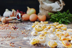 Homemade pasta ravioli on old wooden table with flour, eggs, kit. Chen italian herbs - cooking concept Stock Photos