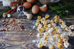 Homemade pasta ravioli on old wooden table with flour, eggs, kit. Chen italian herbs - cooking concept Royalty Free Stock Photography