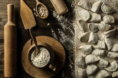 Homemade pasta ravioli over wooden table with flour. Kitchen utensils Stock Image