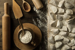 Homemade pasta ravioli over wooden table with flour. Kitchen utensils Stock Photography