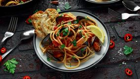 Homemade Pasta Spaghetti with mussels, tomato sauce, chilli and parsley on rustic background. sea food meal.  Royalty Free Stock Image