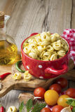 Homemade pasta. Traditional Italian tortellini in a red ceramic saucepan Stock Photos