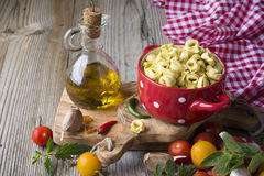 Homemade pasta. Traditional Italian tortellini in a red ceramic saucepan Stock Images