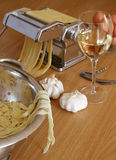 Homemade pasta with wine. Homemade fettuccine pasta with tomatoes and pasta machine in the background stock photo