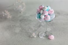 Homemade pastel pink, blue and white meringue in glass on neutral grey background. Horizontal minimalistic composition stock images
