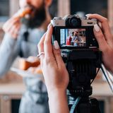 Homemade pastries cooking hobby blogging lifestyle. Homemade pastries. Cooking hobby. Blogging lifestyle. Pleased men eating fresh croissant. Woman with camera stock photo
