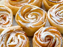 Homemade pastries of flaky unleavened dough. With apples on parchment paper Royalty Free Stock Images