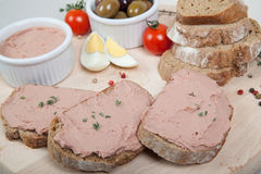 Homemade pate, olives, tomatoes and slices of bread on wooden board Stock Photo