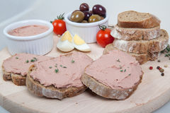 Homemade pate, olives, tomatoes and slices of bread on wooden board Royalty Free Stock Photography
