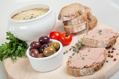 Homemade pate, tomatoes and slices of bread on wooden board Stock Image