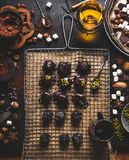 Homemade patisserie. Handmade pralines and truffles making preparation on dark table background with ingredients. Brocken chocolate, various nuts, spices royalty free stock images