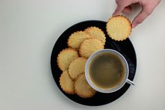 Homemade patterned shortbreads on the black plate and cup with black coffee. Kids hand holding one cookie. Top view. stock photography