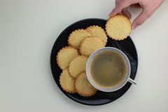 Homemade patterned shortbreads on the black plate and cup with black coffee. Kids hand holding one cookie. Top view. royalty free stock image