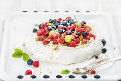 Homemade Pavlova cake with fresh garden and forest berries on white baking tray over light backdrop Royalty Free Stock Photography