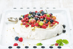 Homemade Pavlova cake with fresh garden and forest berries on white baking tray over light wooden background Stock Photo