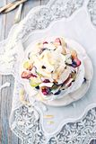 Homemade Pavlova with Fresh Fruits and Coconut; Cake with blueberries, strawberries, grapes, raspberries and coconut royalty free stock image