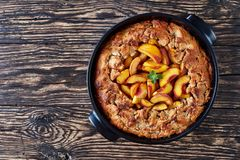 Homemade Peach Cobbler in a black dish. Homemade Peach Cobbler with crisp topping in a black dish, made from fresh summer peaches, horizontal view from above stock images