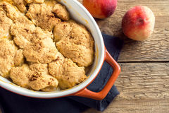 Homemade peach cobbler. (crumble) in baking dish over rustic wooden background royalty free stock photo