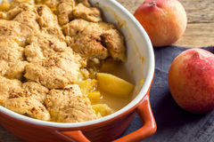 Homemade peach cobbler. (crumble) in baking dish over rustic wooden background royalty free stock photos