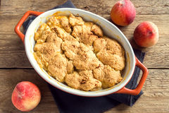 Homemade peach cobbler. (crumble) in baking dish over rustic wooden background royalty free stock photography
