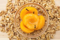 Homemade peach compote spiced with cloves in a glass bowl with walnut pieces scattered around stock image