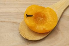 Homemade peach compote spiced with cloves in a glass bowl on wooden spoon and background royalty free stock photography