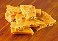 Homemade Peanut Brittle. Traditional homemade peanut brittle displayed on a wood tray Stock Images