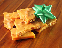 Homemade Peanut Brittle with Green Bow. Traditional homemade peanut brittle displayed on a wood tray with a green bow Stock Photography