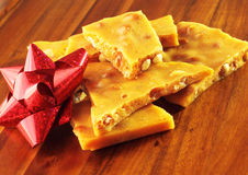 Homemade Peanut Brittle with Red Bow. Traditional homemade peanut brittle displayed on a wood tray with a red bow Stock Images