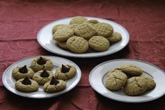 Homemade peanut butter and chocolate drop cookies. Fresh baked cookies. close up Three types of cookies. White plates on table with red tablecloth royalty free stock images