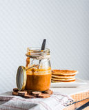 Homemade peanut butter in a glass jar, eat a teaspoon Royalty Free Stock Images
