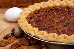 Homemade pecan pie with ingredients. A homemade pecan pie with pecans, white and brown eggs Royalty Free Stock Photo