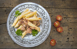 Homemade Penne pasta with tuna sauce in silver plate on old wood Royalty Free Stock Images