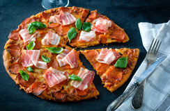 Homemade Pepperoni Pizza with fresh bacon over black background.  Stock Images