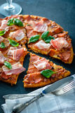 Homemade Pepperoni Pizza with fresh bacon over black background. Top view Stock Images