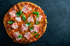 Homemade Pepperoni Pizza with fresh bacon over black background. Top view Stock Image