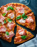 Homemade Pepperoni Pizza with fresh bacon over black background. Top view Royalty Free Stock Images