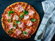 Homemade Pepperoni Pizza with fresh bacon over black background. Top view Royalty Free Stock Photo